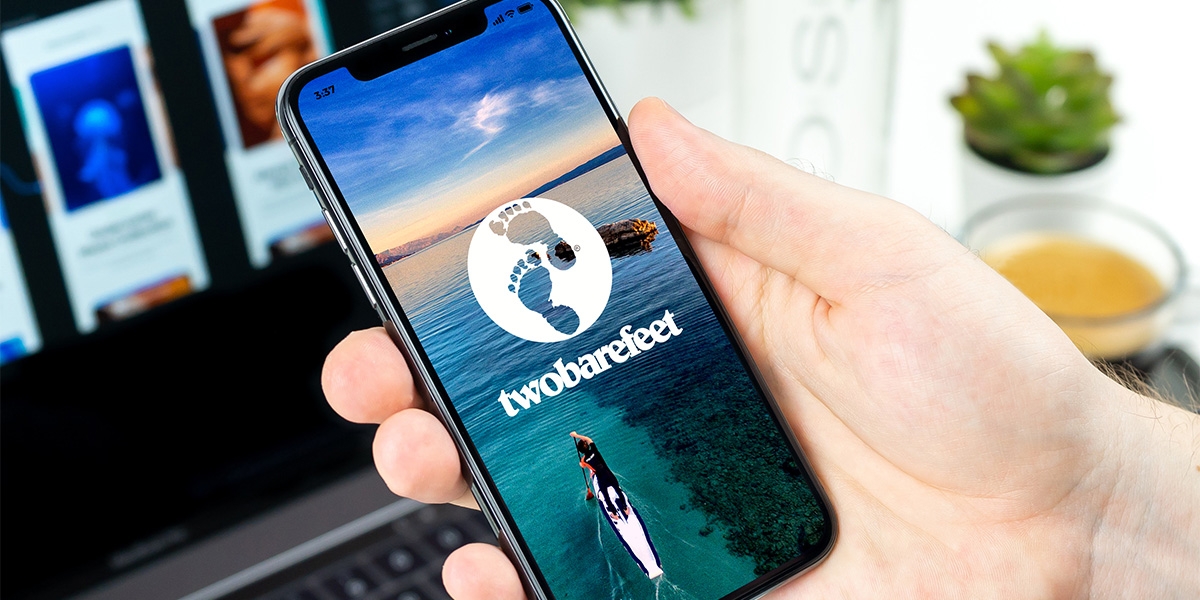 Phone displaying Two Bare Feet logo featuring paddleboarder on SUP in open water