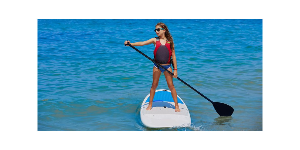 Child standing on inflatable paddle board with SUP paddle in hands