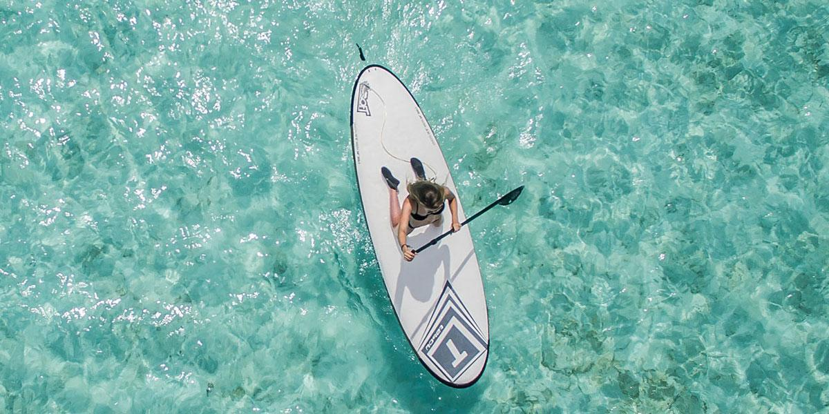 Woman paddle boarding in tropical waters