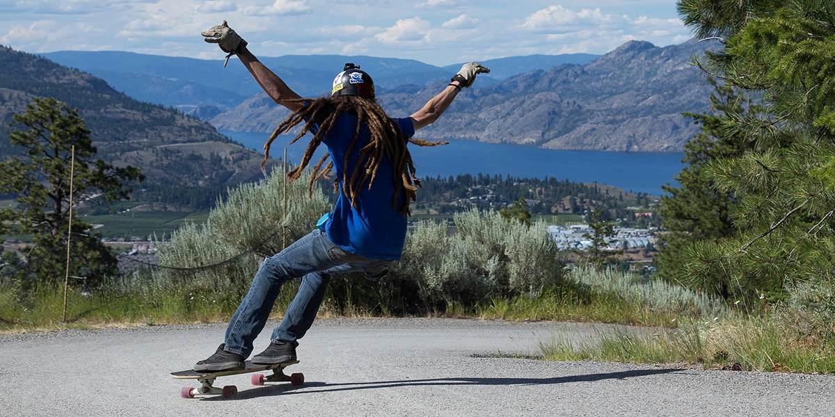 longboarder sliding around a corner on a steep hill