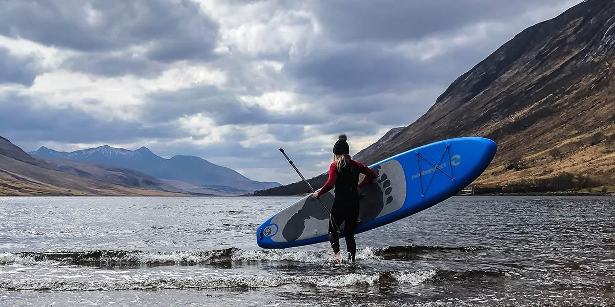girl carrying an inflatable sup into a cold scottish loch