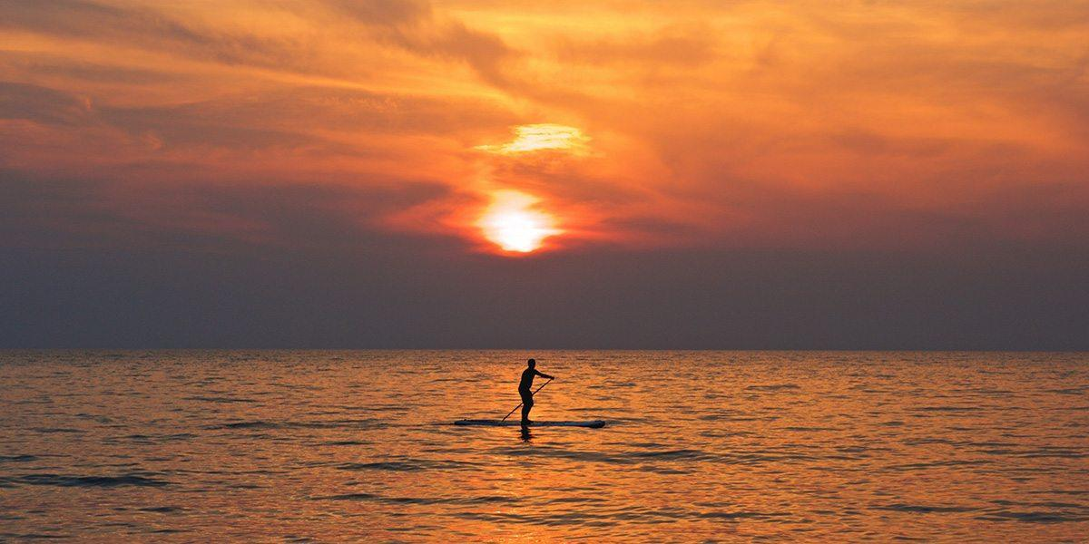 man paddleboarding at sunset on the sea