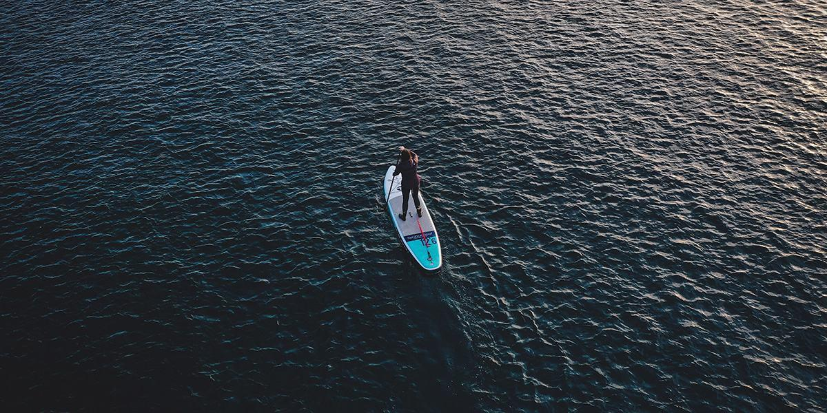 paddleboarding paddling a touring sup in the ocean photographed by a drone