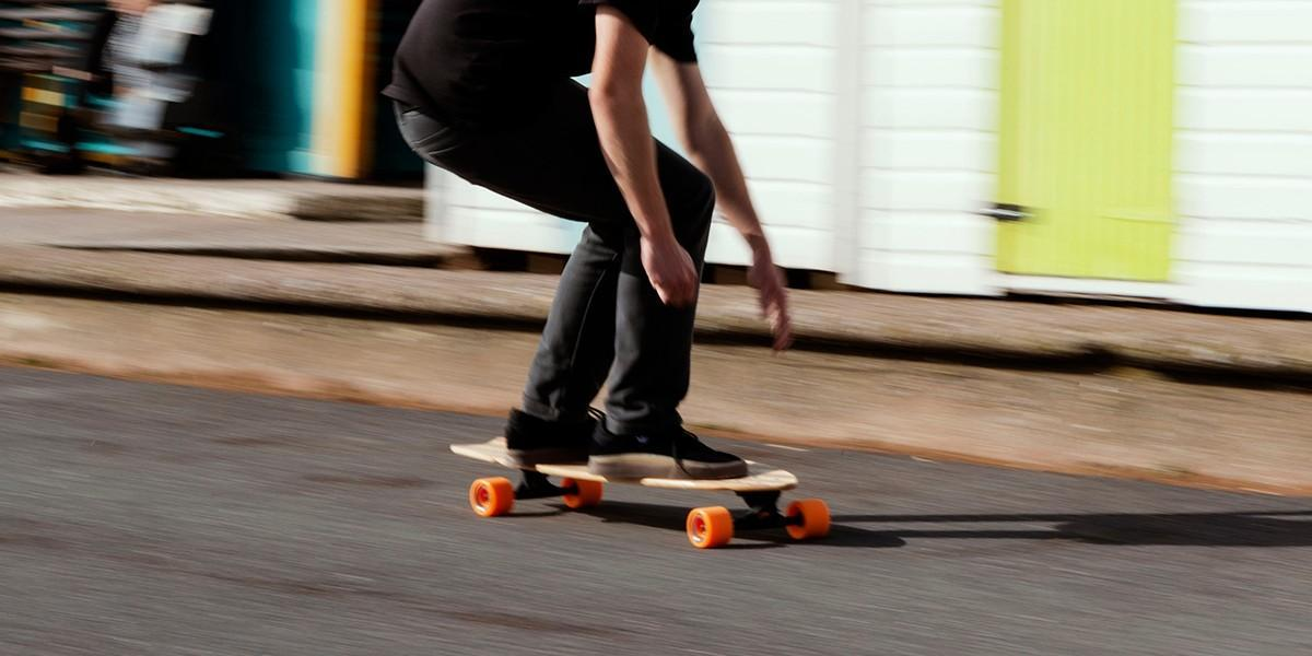 skater cruising on a longboard passed beach huts
