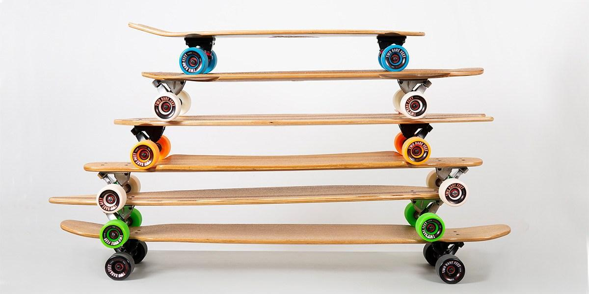 a stack of different sized bamboo longboards and skateboards