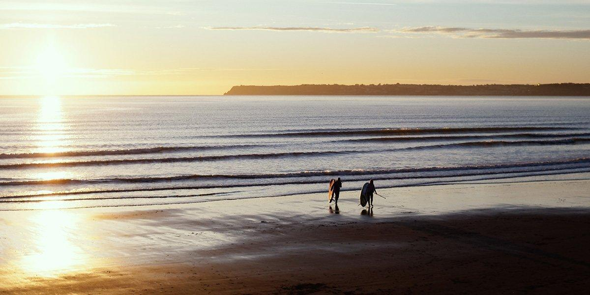 two paddleboarders walking down the beach towards the sea at sunrise