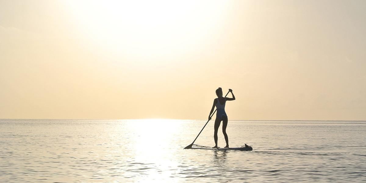 paddleboarder on glassy water during sunset