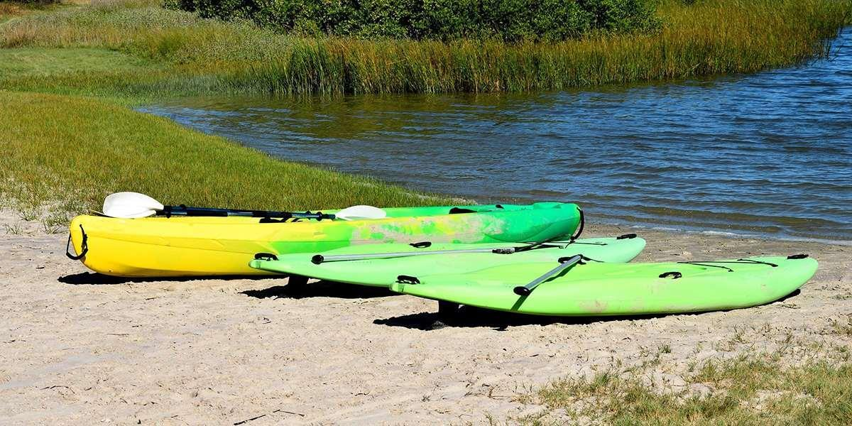 two sups and one kayak on the beach at a lake
