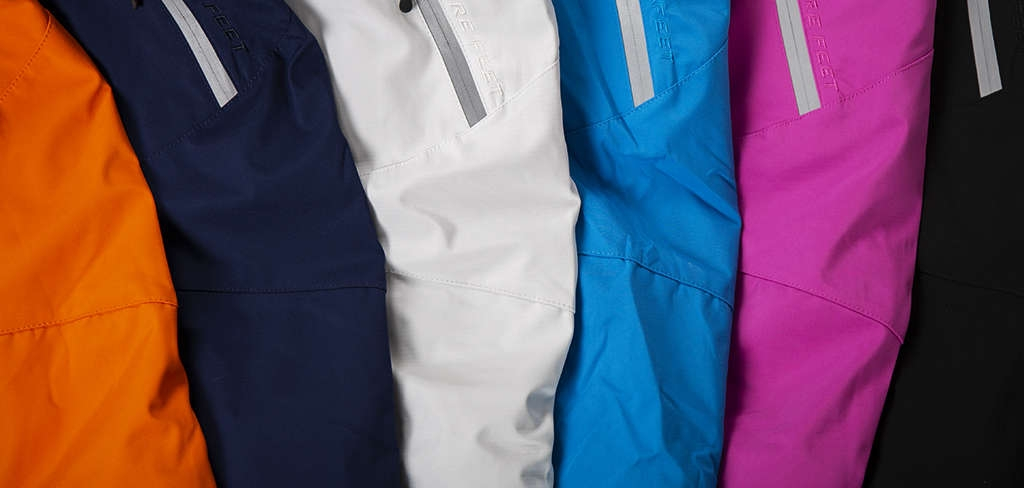 Close up of black, purple, blue, silver, navy and orange ski jackets